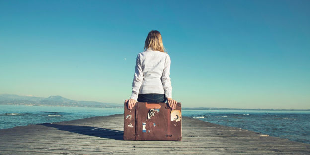 woman sitting on suitcase looking at water