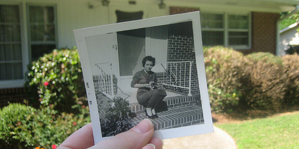 Photo held in front of house that overlaps with a present day scene