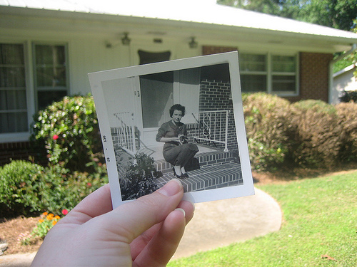 Person holding an old photo that overlaps with a present day scene